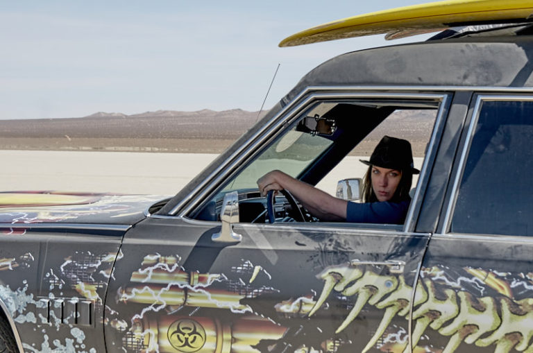 Amanda Wing driving the big hearse on the dry lake bed.